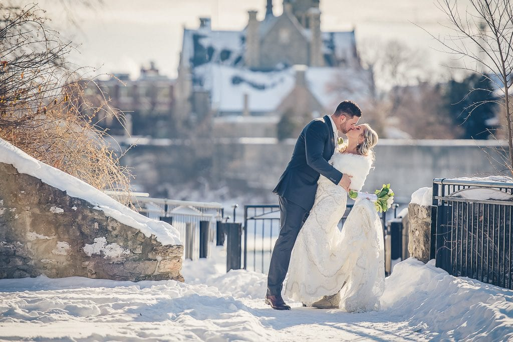 Bride and groom kissing in mill race park in the winter in Cambridge Ontario