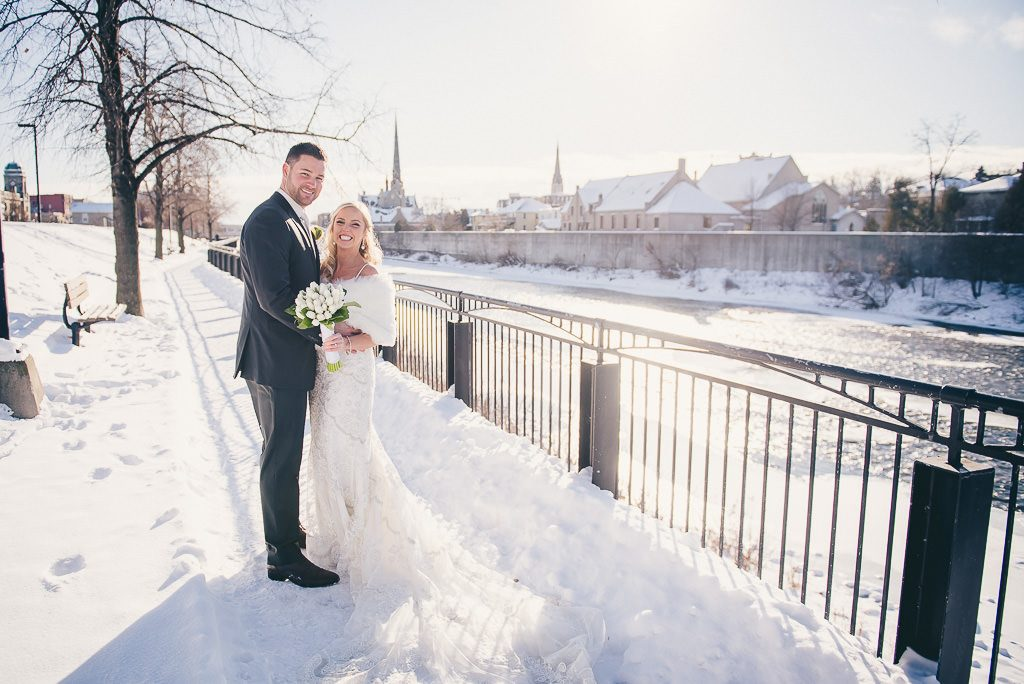 bride and groom posing for photo in the snow in Mill Race Park in Cambridge