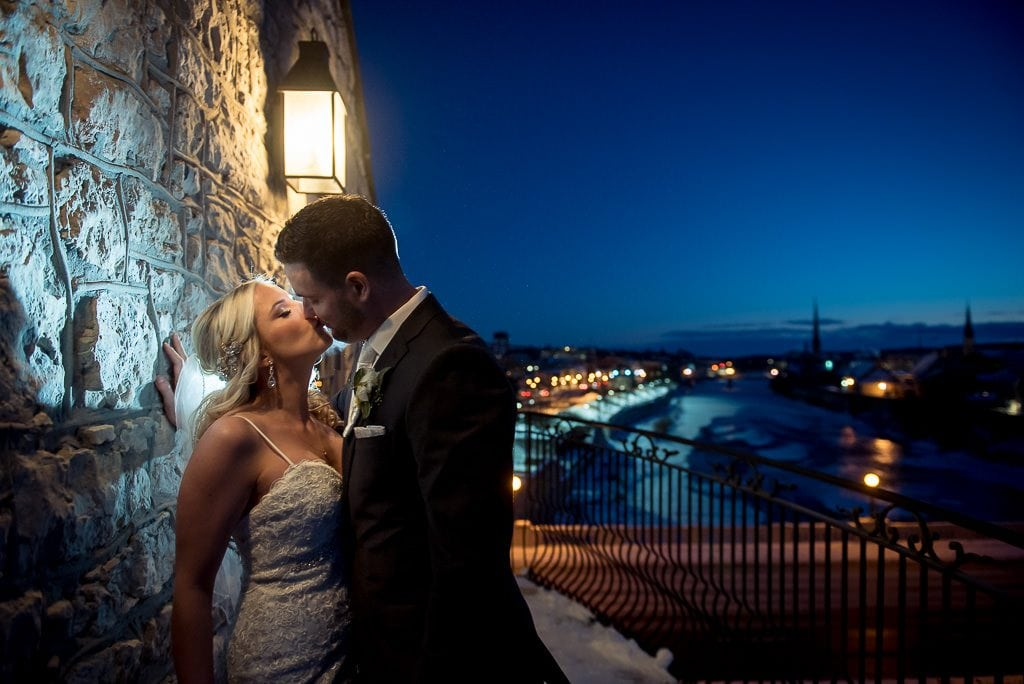 bride and groom kissing on the balcony at the Cambridge Mill