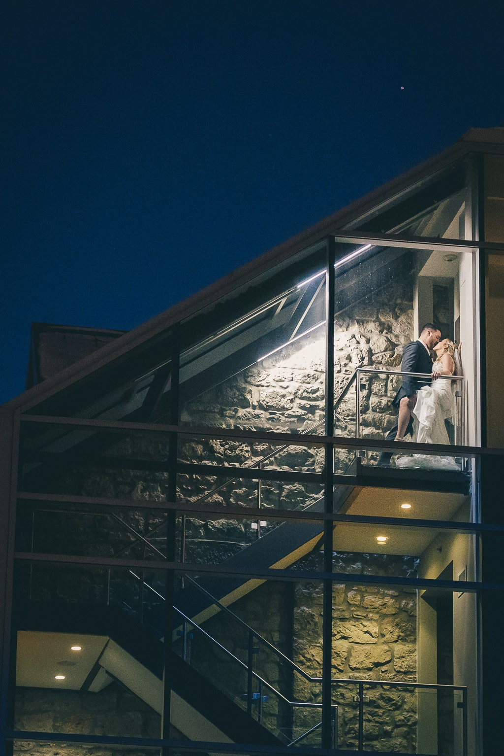 bride and groom kissing in the stairs at the Cambridge Mill