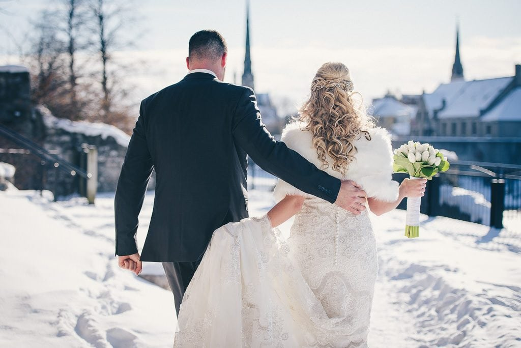 Bride and groom walking in the snow for their winter wedding in Cambridge
