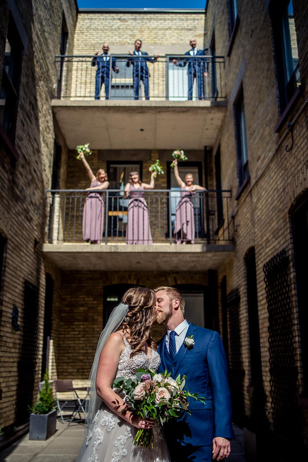 bridal party cheering from balcony of walper hotel wedding